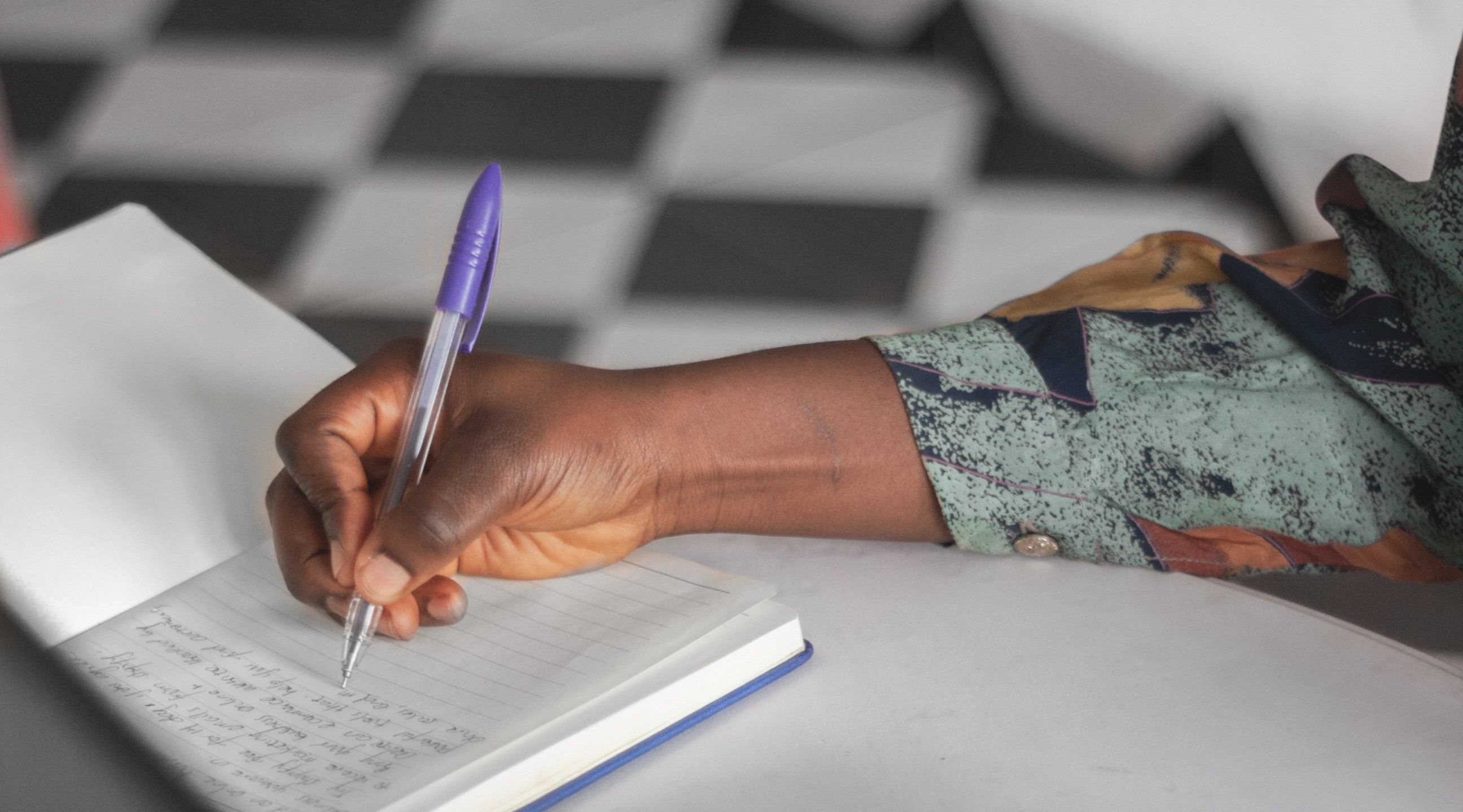 Blog_Lockdown_OneYearOn_hand-writes-in-a-notebook-by-a-laptop-and-cellphone_PhotoCredit_Joshua Bamidele_Burst_Shopify_Banner